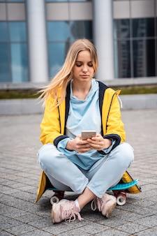 Красивая женщина использует смартфон и сидит на скейтборде