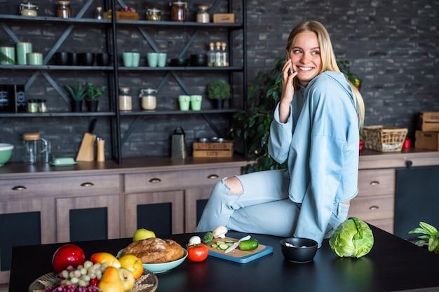 Красивая женщина разговаривает по мобильному телефону на кухне у себя дома