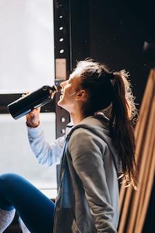 Красивая девушка пила воду из пластиковой бутылки, теплое солнечное утро
