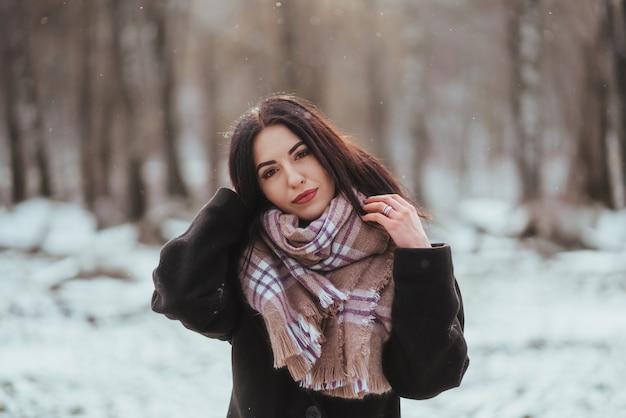 Молодая красивая модель позирует в зимнем лесу