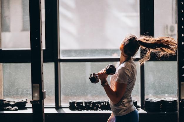 Стройная спортивная девушка выполняет физические упражнения с гантелями.
