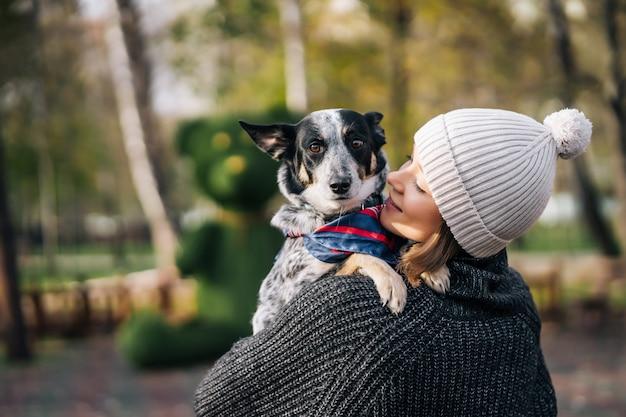 雑種犬を腕に抱えている少女。動物の世話をする。