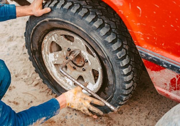 Человек откручивает болты на колесе