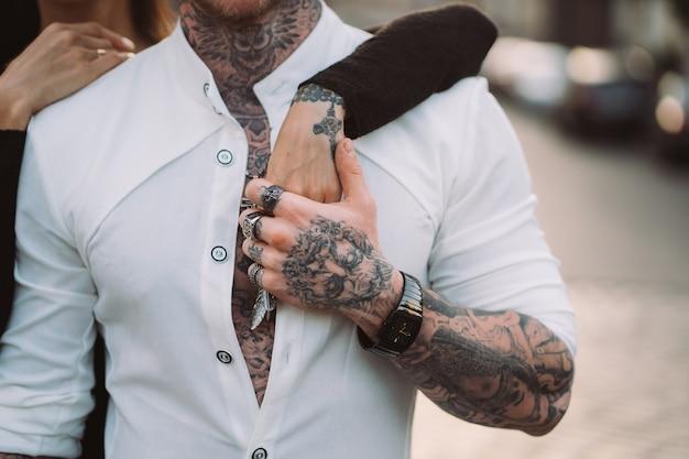 Мужчина держит женскую руку на своем торсе