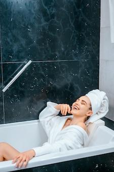 Расслабленная женщина с полотенцем на волосах лежит в ванной