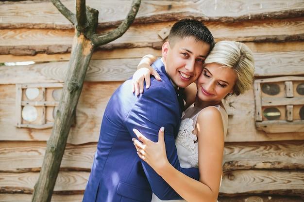 Красивая молодая свадебная пара стоит возле дома