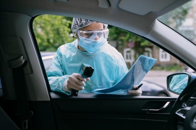 Доктор женщина использовать инфракрасный термометр пистолет для проверки температуры тела