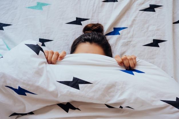 毛布で覆われたベッドに横たわっている素敵な若い女性