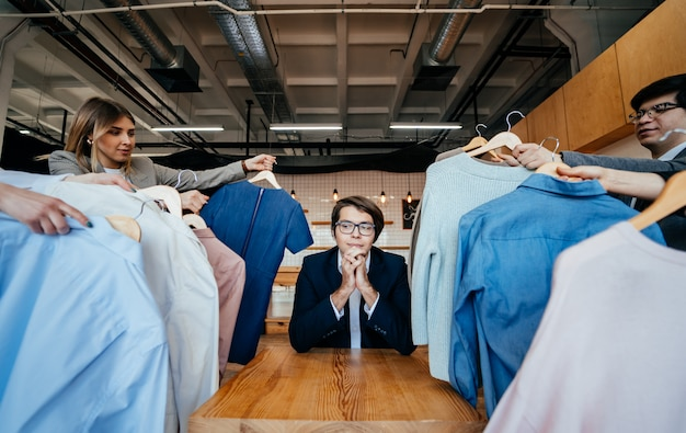 ファッション撮影のためのシャツのセットを探している若いスタイリスト