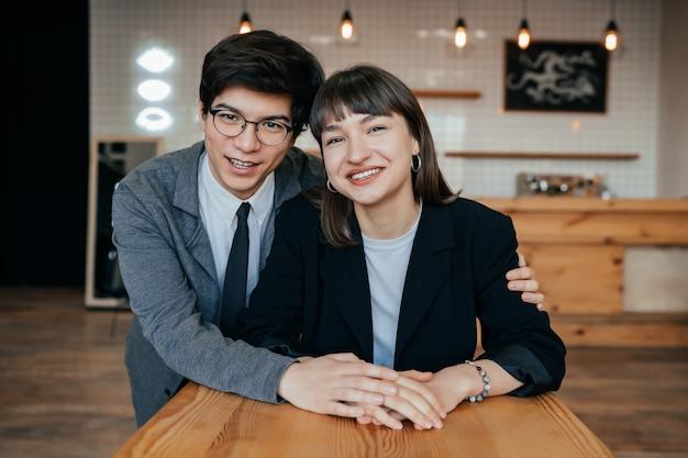 Молодая пара позирует в офисе