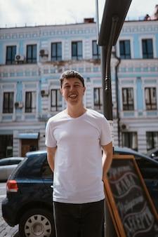 Человек в серой футболке и джинсах на фоне городской улицы