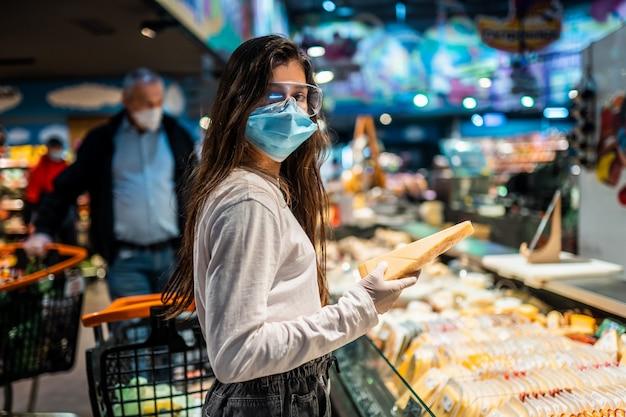 サージカルマスクの女の子がチーズを購入します。