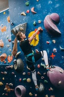 Молодая женщина, взбирающаяся на высокую крытую искусственную скалолазную стену