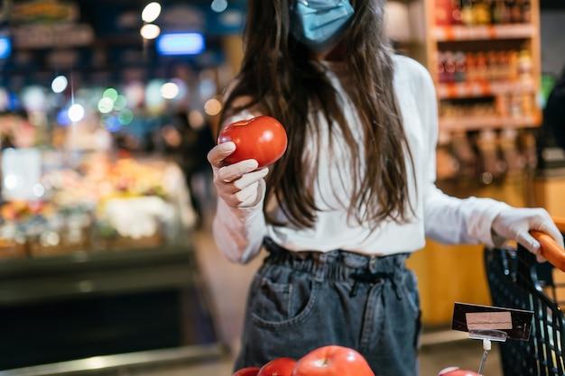 サージカルマスクを持つ女性はトマトを購入する予定です。