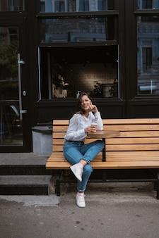ストリートカフェの美しい若い女性はコーヒーを飲む