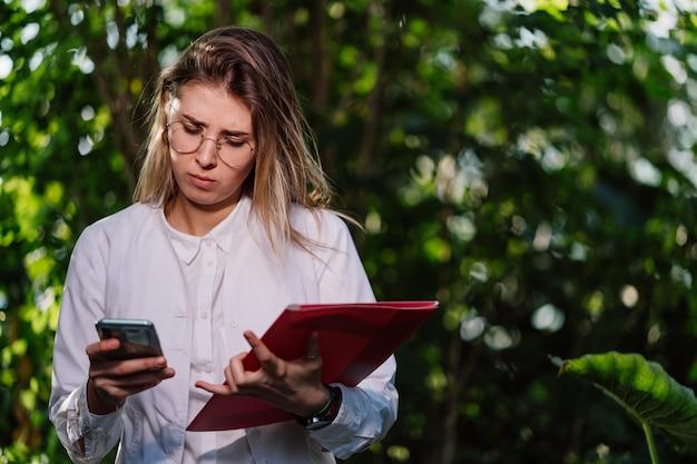 若い女性農業技術者が温室で電話をかける