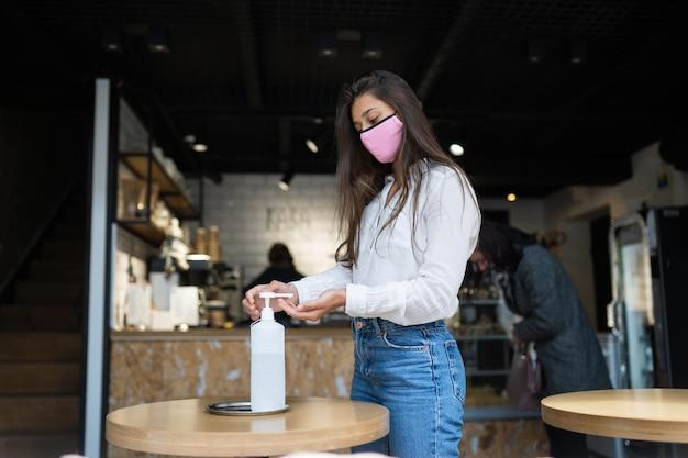 消毒ジェルを使用している女性がカフェでコロナウイルスの手をきれいにする