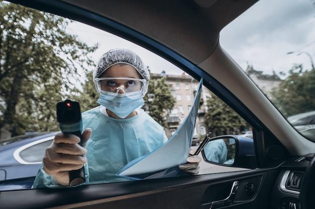 医師の女性は体温をチェックするために赤外線温度計銃を使用します