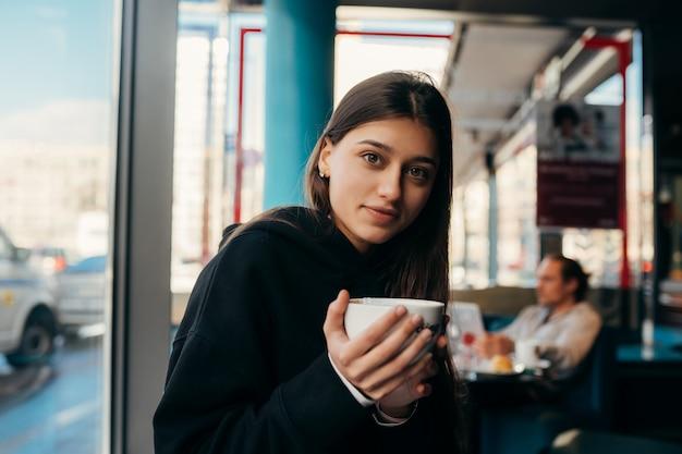 Близкий портрет кофе выпивая довольно вверх по женщине