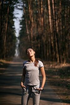 フィットネス若い女性が公園を散歩し、カメラにポーズ