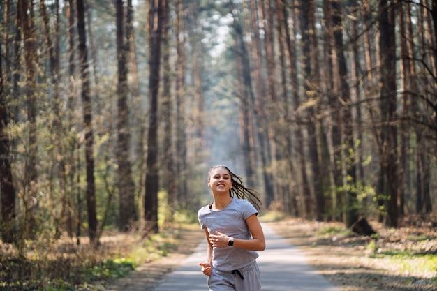 日当たりの良い夏の日に緑豊かな公園で走っている美しい若い女性
