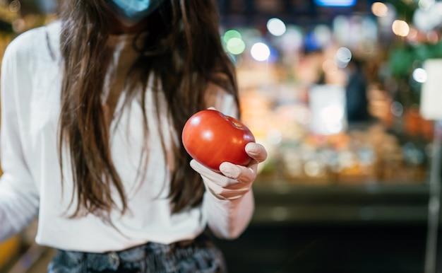 サージカルマスクと手袋をした女性が、コロナウイルスのパンデミックの後にスーパーマーケットで買い物をしています。サージカルマスクを持つ少女はトマトを買うつもりです。