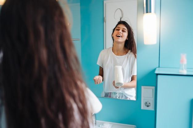 Портрет молодой женщины используя фен для волос в ванной комнате. веселиться