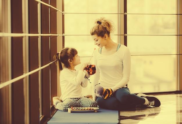 彼女の小さな娘と一緒に遊んで若い母