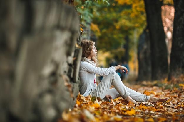 Задумчивый молодая женщина, сидя на сухих листьев