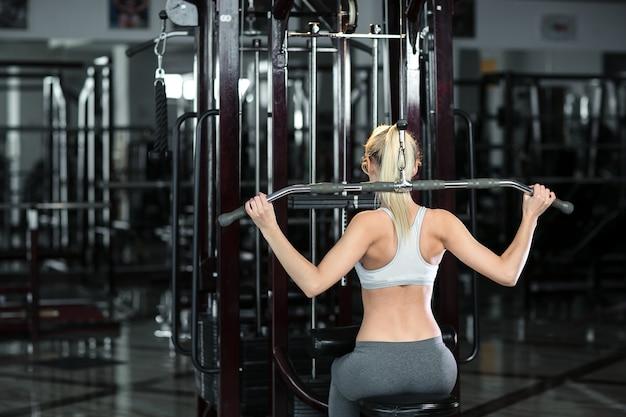 ジムで金属製の棒を持つ女性の背面図