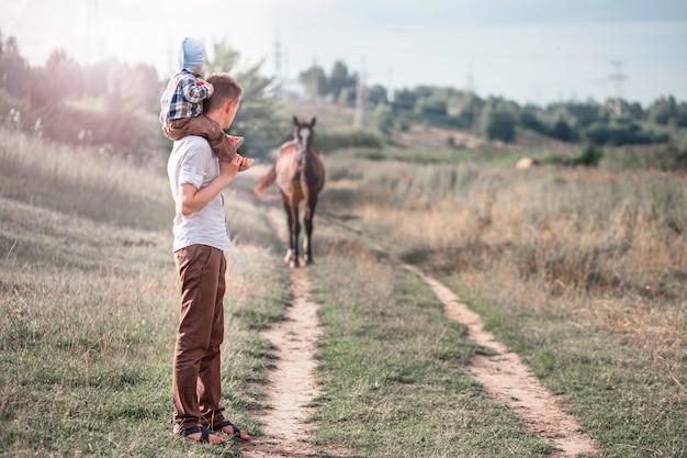 幼い息子と彼のお父さんが馬を見て