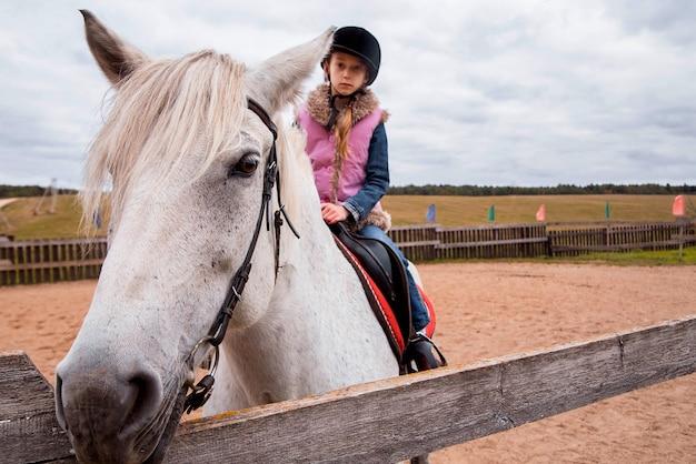 Маленькая девочка верхом на лошади на ферме