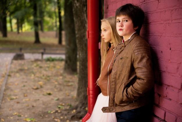 Мальчик и девочка подростков позирует на фоне кирпичной стены