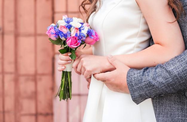 新郎新婦。花嫁は彼女の手に花束を持っています