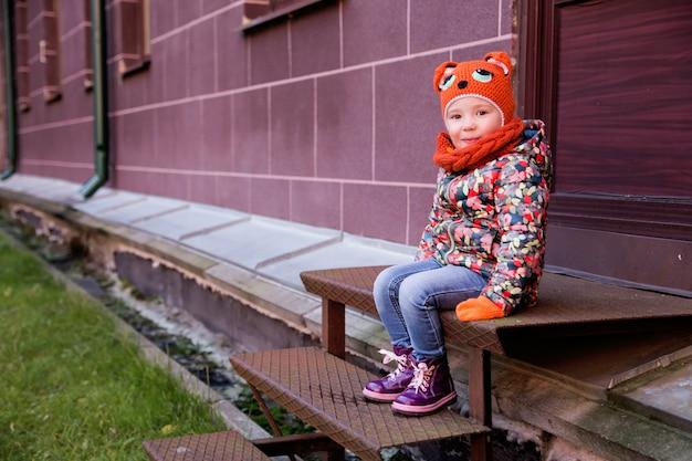 小さな女の子は家のポーチに座っています。
