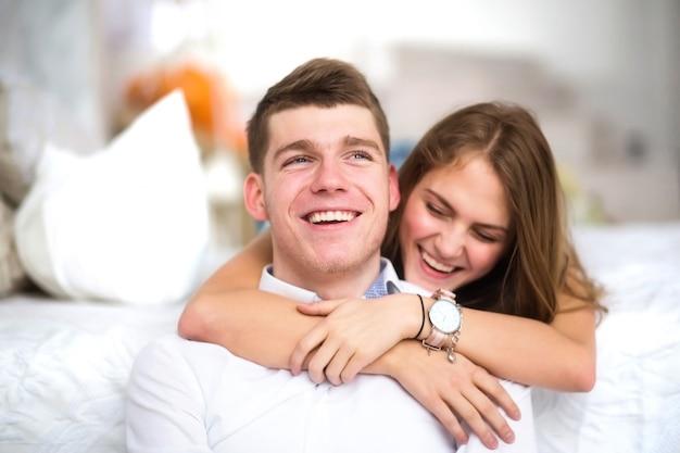 Счастливая девушка в любви дома обнимает парня