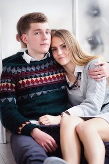 ミラーの壁に座っているティーンエイジャーのカップル