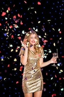 Счастливая молодая женщина в вечернем платье празднует на черном фоне