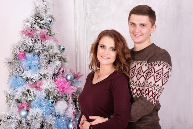 新年一緒に笑顔を祝うクリスマスツリーの近くを受け入れる若い幸せなカップル