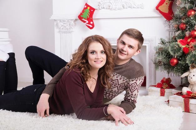 カーペットの上の素敵な愛のカップル。女と男のクリスマスを祝う