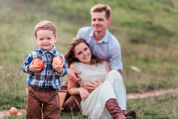 ピクニックで幸せな家族。フォアグラウンドでリンゴと小さな男の子