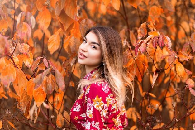 秋をテーマにポーズをとって赤いドレスで美しい少女
