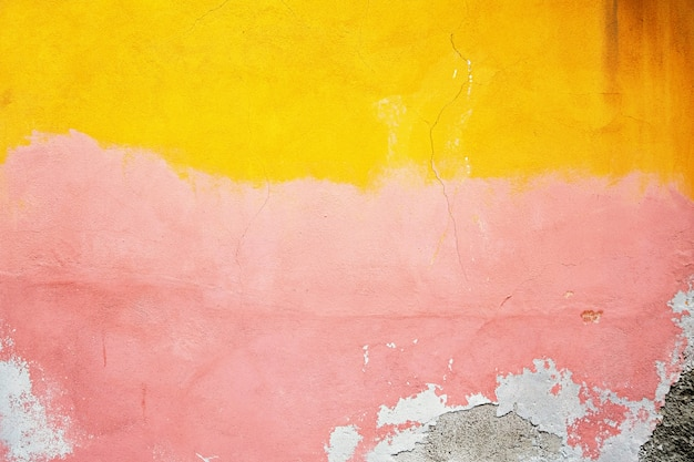Желтая, розовая, серая разрушенная штукатурка у кирпичной стены. гранж цемент, с потертой краской фоне.