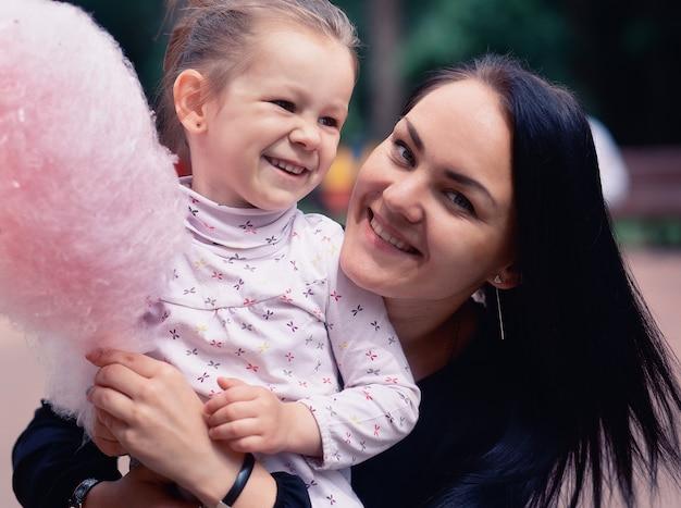Мама и дочка в парке едят сладкую вату