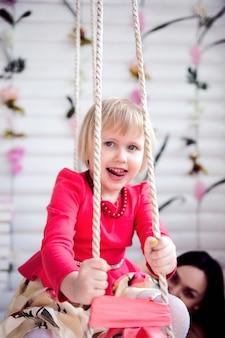 Очаровательны маленькая девочка с удовольствием на качелях.