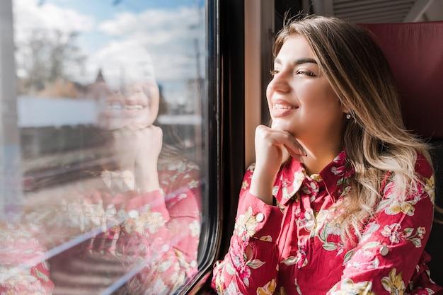 Красивая девушка сидит одна в поезде и весело смотрит в окно