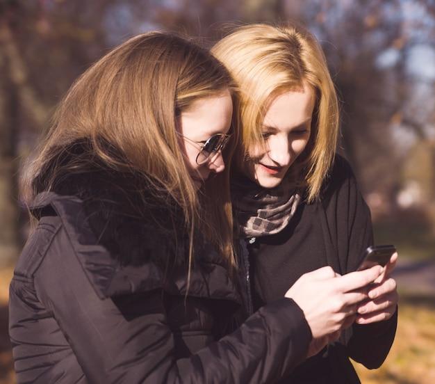 Две счастливые подруги общаются в социальных сетях в смартфоне на открытом воздухе в парке