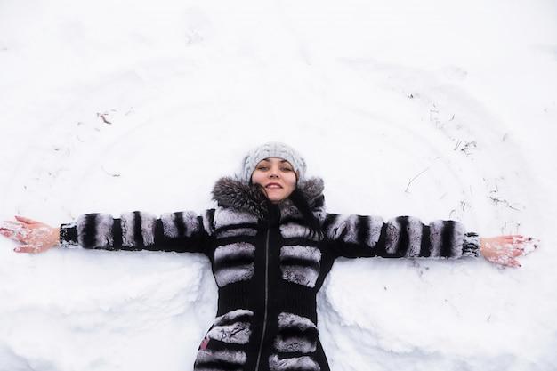 Счастливая молодая женщина, лежа на меху снега в зимнее время