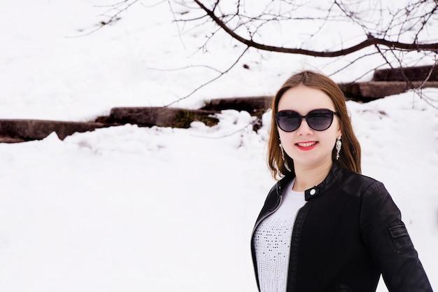 Женщина в зимнем парке в темных очках и куртке