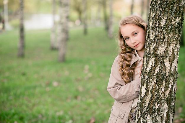 木の近くに立っている美しい少女の肖像画